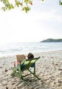 mujer leyendo en playa